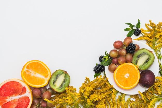 Gehalveerde vruchten; druiven; braambessen en gele mooie bloemen op witte achtergrond Gratis Foto