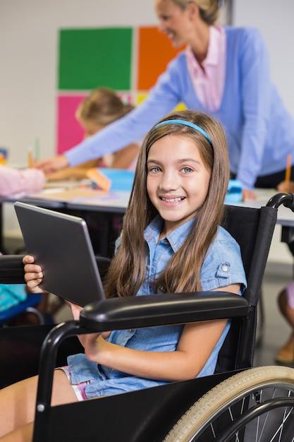 Gehandicapt schoolmeisje dat digitale tablet gebruikt Premium Foto