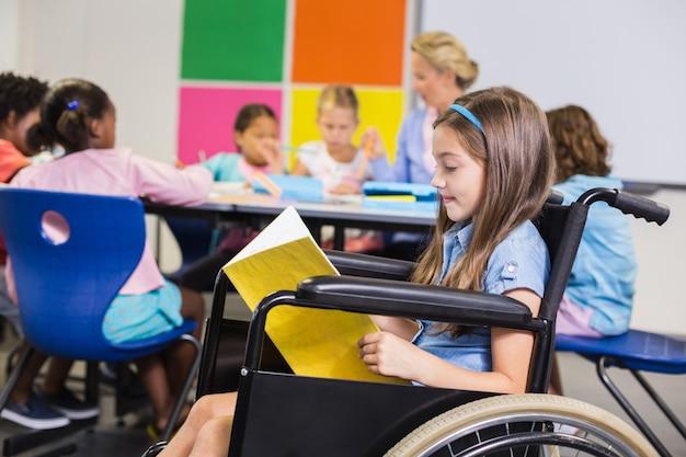 Gehandicapt schoolmeisje die op rolstoel een boek in klaslokaal lezen Premium Foto