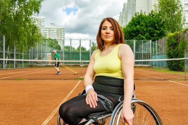 Gehandicapte jonge vrouw op rolstoel tennissen op tennisbaan. Premium Foto