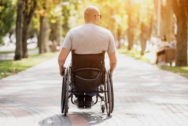 Gehandicapte man in rolstoelwandeling op het steegje van het park Premium Foto