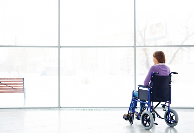 Gehandicapte vrouw die venster bekijkt Gratis Foto
