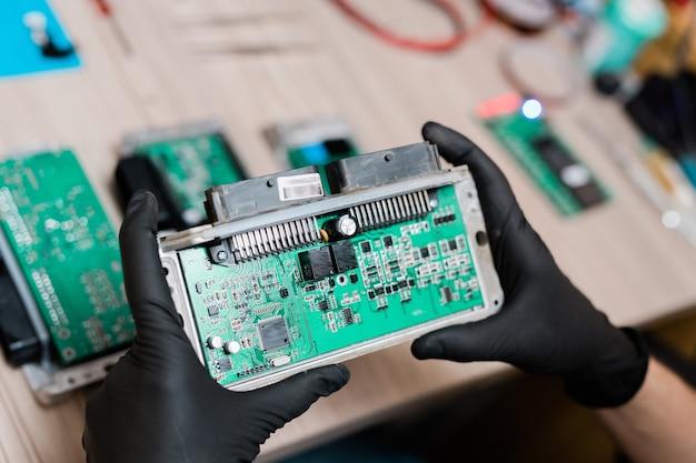 Gehandschoende handen van de reparatiedienstmeester die een deel van de gedemonteerde gadget vasthoudt terwijl hij deze onderzoekt en probeert de oorzaak van de breuk te achterhalen Premium Foto