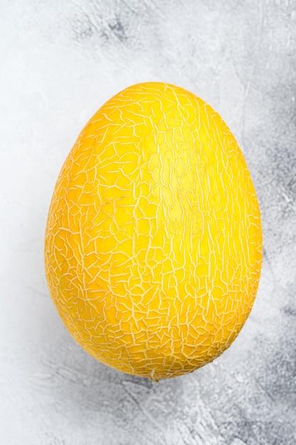 Geheel gele rijpe meloen. witte achtergrond. bovenaanzicht. Premium Foto