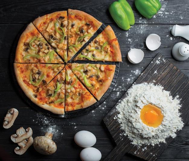Geheel gesneden pizza en het maken van pizzadeeg met bloem en ei Gratis Foto