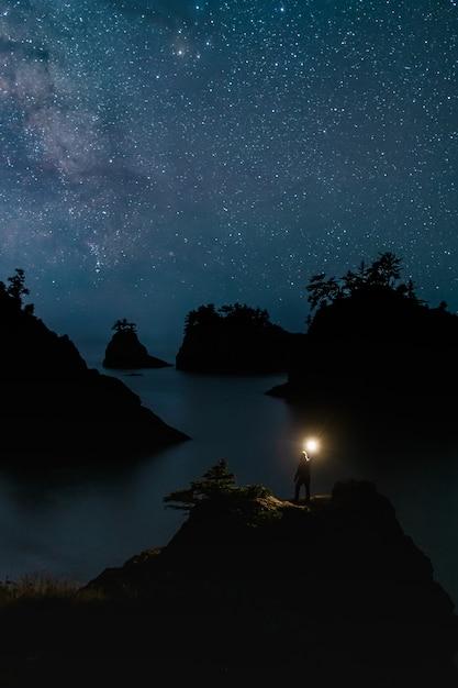 Geheim strand oregon bij nacht met sterren en reiziger permanent met het licht Premium Foto
