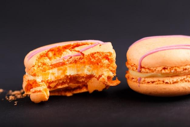 Gehele en gebeten oranje macarons of makaronscakes op zwarte achtergrond Premium Foto