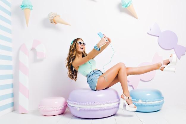 Geïnspireerd grappig meisje tank-top en denim shorts zittend op speelgoed macaron dragen en selfie maken. jonge dame lachen in zonnebril en koptelefoon nemen foto van zichzelf in kamer met lief interieur. Gratis Foto