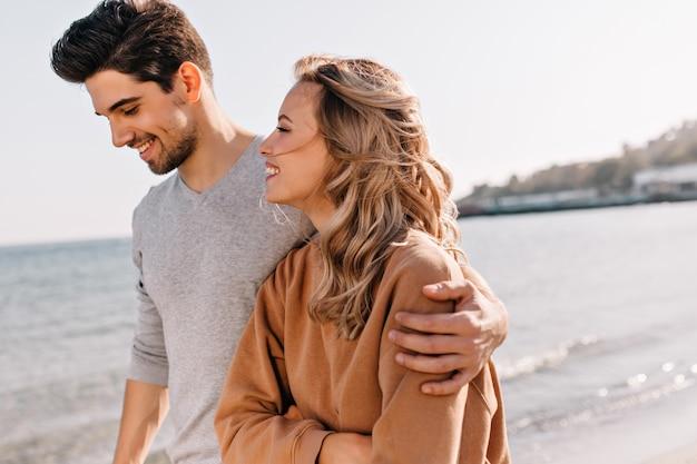 Geïnspireerd jongeman vriendin omarmen tijdens wandeling op strand. nieuwsgierige blonde vrouw weekend doorbrengen op zee. Gratis Foto