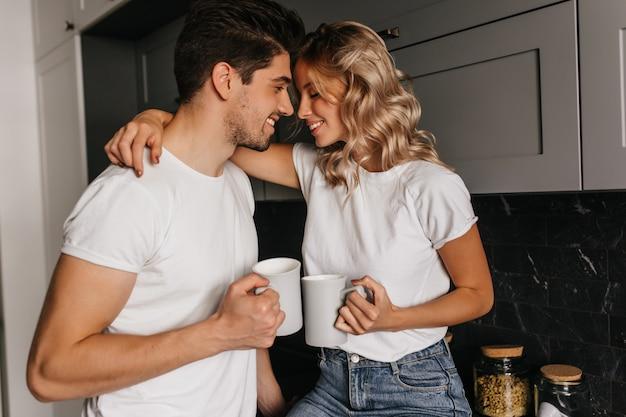 Geïnspireerd meisje dat van ochtend met echtgenoot geniet. indoor portret van koelende paar koffie drinken. Gratis Foto