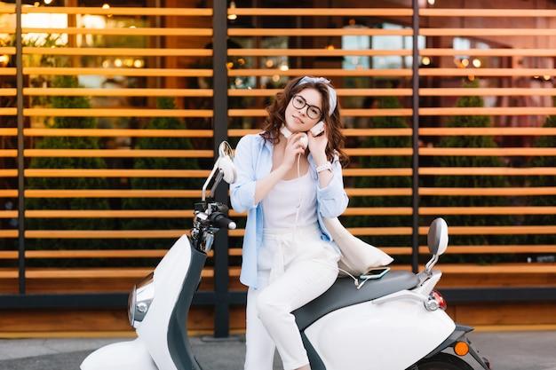 Geïnspireerd slank meisje met stijlvol kapsel zittend op scooter klaar om in het weekend door de stad te rijden Gratis Foto