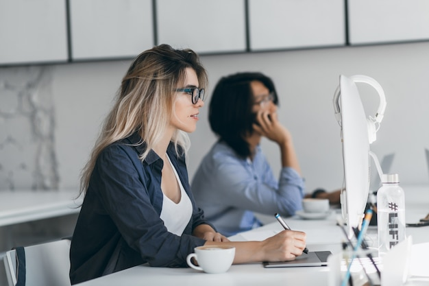 Geïnspireerde freelance webdesigner met behulp van tablet en stylus, kijkend naar het scherm terwijl haar vriend aan het bellen is. aziatische student smartphone houden en typen op toetsenbord, zittend naast blond meisje. Gratis Foto