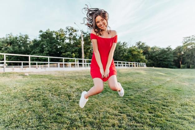 Geïnspireerde jonge vrouw die in park springt en glimlacht. mooie brunette meisje in een rode jurk plezier in zomerweekend. Gratis Foto