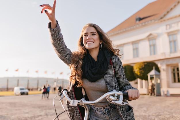 Geïnspireerde jonge vrouw in zwarte sjaal rijden op de fiets rond de europese stad Gratis Foto