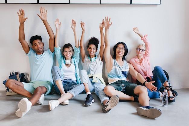 Geïnspireerde studenten poseren graag met hun handen omhoog omdat examens voorbij zijn. binnenportret van zalige universiteitsgenoten die voor de vakantie plezier hebben op de campus. Gratis Foto