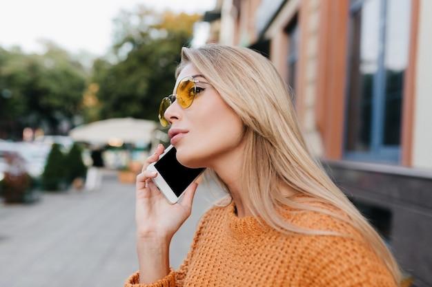 Geïnspireerde vrouw met lang blond haar die iemand belt en in de verte kijkt Gratis Foto