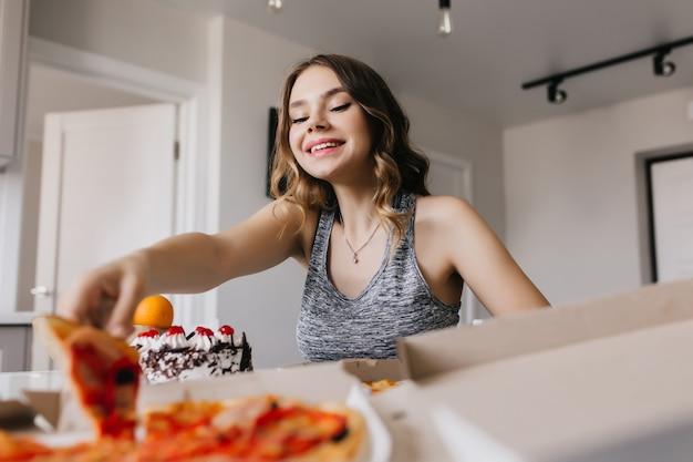 Geïnteresseerd meisje met golvend kapsel pizza eten met plezier. betoverend vrouwelijk model zittend in de keuken en genieten van fast food. Gratis Foto