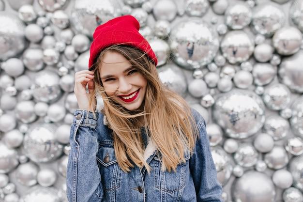 Geïnteresseerd mooi meisje in spijkerjasje wat betreft haar lange haar. glimlachend europees vrouwelijk model in hoed poseren op glanzende muur. Gratis Foto