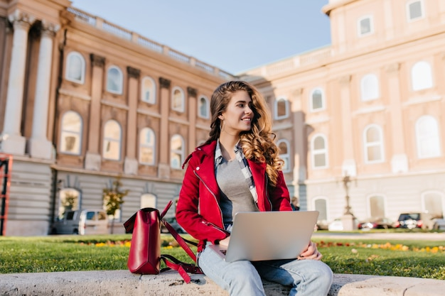 Geïnteresseerde donkerharige meisje draagt casual kleding chillen in park in de buurt van de universiteit en laptop gebruikt Gratis Foto
