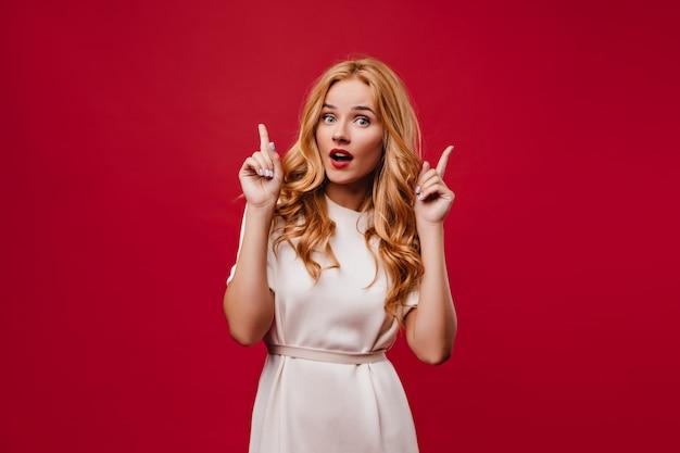 Geïnteresseerde jonge vrouw met lang golvend haar poseren met open mond. debonair stijlvol meisje in witte jurk staande op rode muur. Gratis Foto