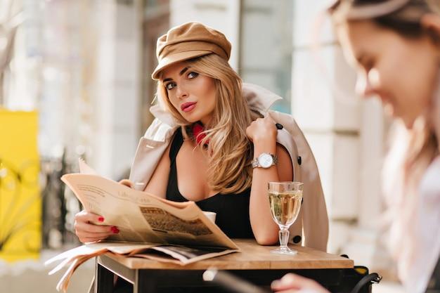 Geïnteresseerde jonge vrouw rondkijken, krant vasthouden en wijn drinken. outdoor portret van mooi meisje draagt glb en stijlvolle beige jas in koude dag tijdens rust in café. Gratis Foto
