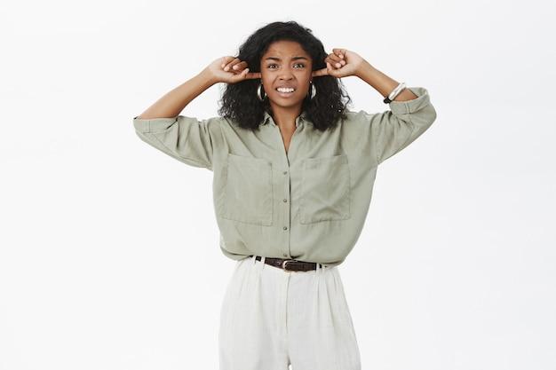 Geïrriteerde, ontevreden en pissige jonge aantrekkelijke vrouw met een donkere huid die zich gestoord voelt door luid irritant geluid Gratis Foto