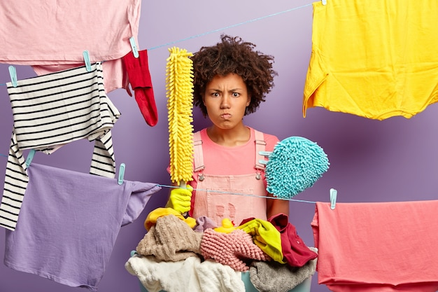 Geïrriteerde ontevreden vrouw heeft afro-kapsel, houdt wasgereedschap vast, staat in de buurt van touwen met opgehangen schone kleren om te drogen, bezig met huishoudelijk werk, boos op dagelijkse klusjes in huis. huishoudelijk concept Gratis Foto