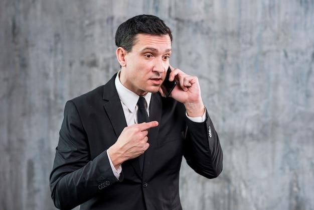 Geïrriteerde volwassen zakenman die op telefoon spreekt Gratis Foto