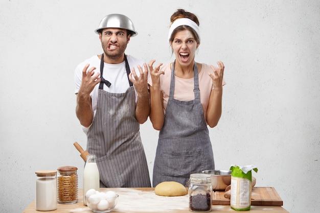 Geïrriteerde vrouwelijke en mannelijke koks, houden handen in woedend gebaar, geïrriteerd door chef-kok Gratis Foto