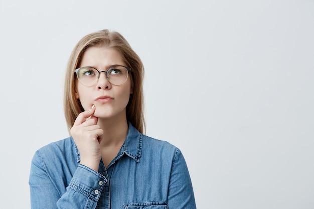 Geïsoleerd portret van stijlvol jong blondemeisje in denimoverhemd en oogglazen wat betreft haar kin en zijdelings kijkend met twijfelachtige en sceptische uitdrukking, vermoedend haar vriend van liegen tegen haar Gratis Foto