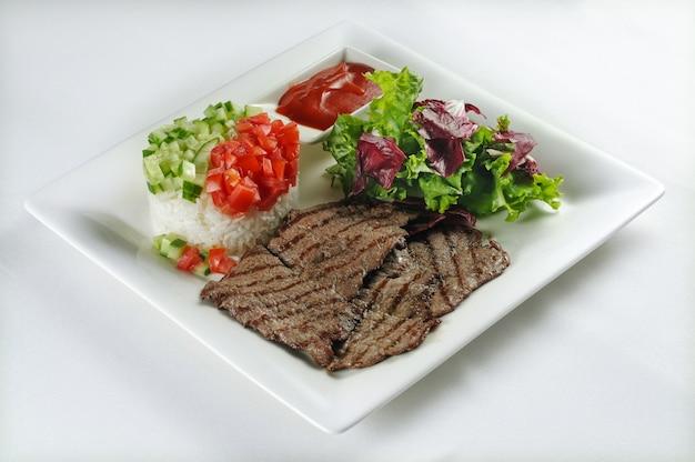 Geïsoleerd schot van biefstuk met rijst, salade en sla - perfect voor een foodblog of menugebruik Gratis Foto