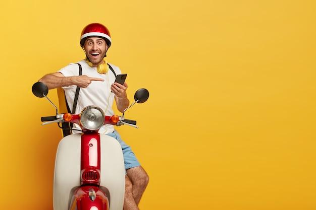 Geïsoleerd schot van gelukkige knappe mannelijke bestuurder op autoped met rode helm Gratis Foto