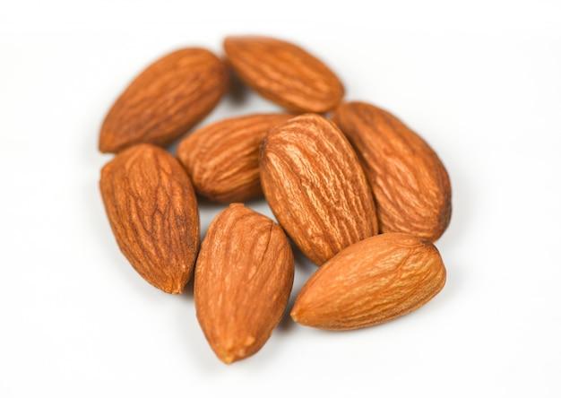 Geïsoleerde amandel - noten op wit natuurlijk eiwitvoedsel en voor snack, selectieve nadruk Premium Foto