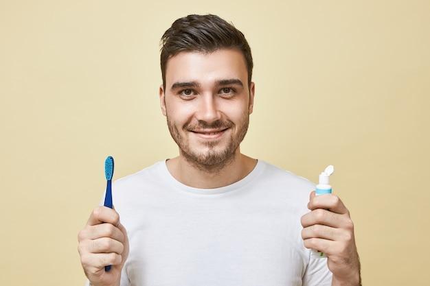 Geïsoleerde beeld van zelfverzekerde vrolijke jonge brunette man met borstel en tube tandpasta, tanden poetsen direct na het ontwaken. hygiëne, ochtendroutine en tanden bleken concept Gratis Foto