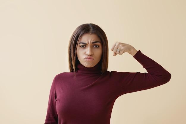 Geïsoleerde foto van aantrekkelijke stijlvolle jonge donkere huid vrouw met losse haren met gekke woedende blik, grimassen en gepompt vuist voor haar te houden, klaar om te slaan. feminisme en meisjeskracht Gratis Foto