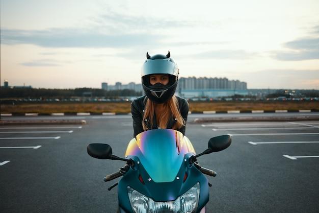 Geïsoleerde foto van blonde vrouwelijke motor racer in speciale beschermingsmiddelen zittend op blauwe motor. extreme, snelheid, adrenaline en moderne actieve levensstijl Gratis Foto