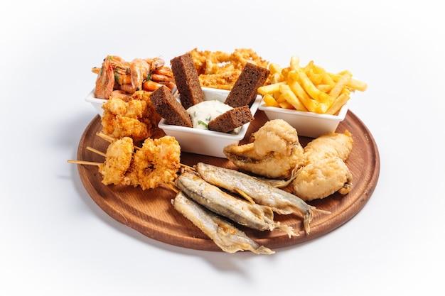 Geïsoleerde gebakken schaal-en schelpdieren bier schotel met vis en garnalen op het houten bord Premium Foto