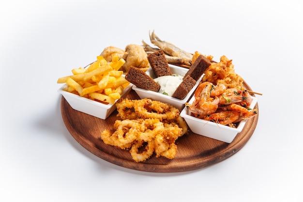 Geïsoleerde gebakken schaal-en schelpdieren bier schotel met vis en garnalen Premium Foto