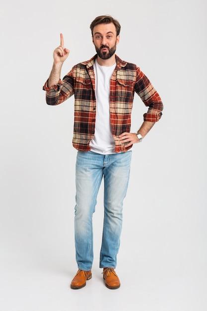 Geïsoleerde lachende knappe bebaarde man wijzende vinger met idee in hipster outfit gekleed in spijkerbroek Gratis Foto