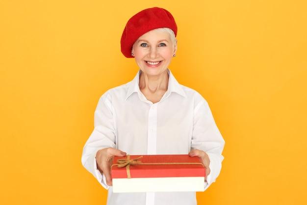 Geïsoleerde portret van mooie gelukkige senior blanke vrouw in elegante kleding poseren op geel Gratis Foto