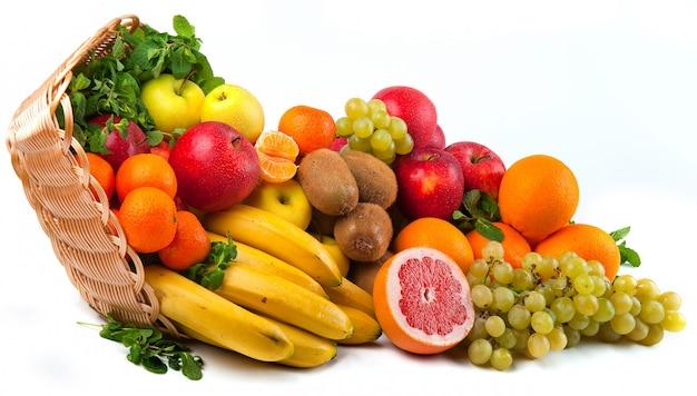 Geïsoleerde samenstelling met groenten en fruit in rieten mand Premium Foto