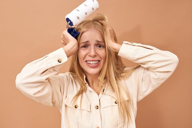Geïsoleerde schot van gefrustreerde ongelukkige jonge vrouwelijke decorateur met beugels hand in hand op haar hoofd met gestreste gezichtsuitdrukking omdat ze de reparatie niet op tijd af heeft Gratis Foto