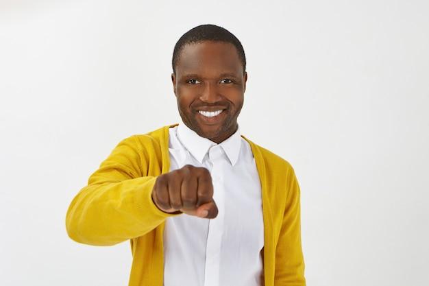 Geïsoleerde schot van gelukkige positieve jonge afro-amerikaanse man met stijlvolle kleding poseren, breed glimlachend en gebalde vuist voor zich houden, klaar om de knokkels te stoten terwijl je wordt begroet Gratis Foto
