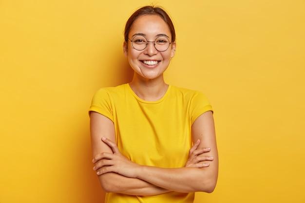 Geïsoleerde schot van tevreden vrolijke vrouw met oosterse uitstraling, breed glimlachend, in goed humeur, vermaakt door grappige vrienden, nonchalant gekleed, draagt een grote transparante bril, geïsoleerd op geel Gratis Foto