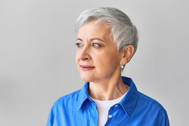 Geïsoleerde shot van aantrekkelijke zestig jaar oude grijze haren vrouw parel oorbellen en blauw shirt dragen over witte top wegkijken met peinzende ernstige gezichtsuitdrukking. mensen en levensstijlconcept Gratis Foto