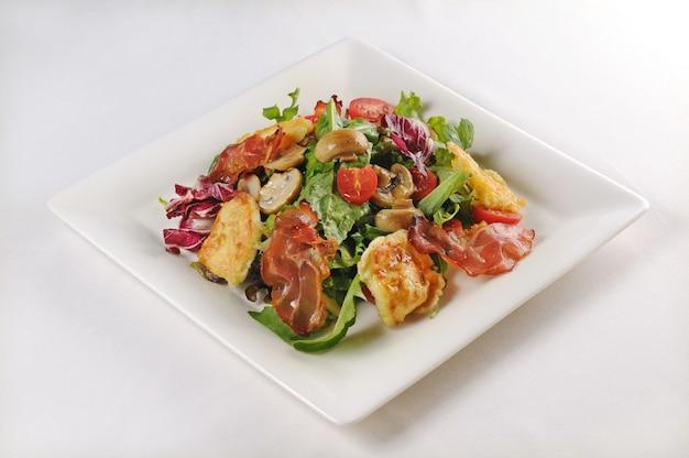 Geïsoleerde shot van een bord met salade met kip en spek - perfect voor een foodblog of menugebruik Gratis Foto