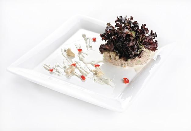 Geïsoleerde shot van een witte plaat met een heerlijke salade - perfect voor een foodblog of menugebruik Gratis Foto