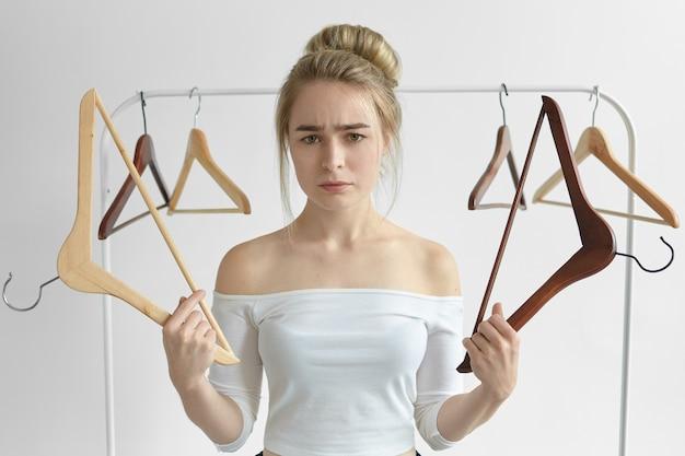 Geïsoleerde shot van gefrustreerde boos jonge vrouw in witte top met lege rekken weet niet wat te dragen op datum, ongelukkig kijken. mensen, levensstijl, kleding, kleding en mode-concept Gratis Foto