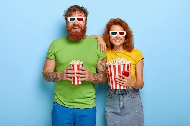 Geïsoleerde shot van gelukkige gember vrouw en haar bebaarde echtgenoot komen in de bioscoop op avondvoorstelling, hebben blije gezichten en glimlachen, dragen een driedimensionale bril, eten heerlijke snack tijdens het kijken naar film Gratis Foto