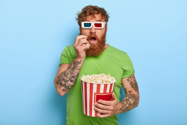 Geïsoleerde shot van knappe man heeft tatoeage, rood haar, kijkt naar film, betrokken bij verhaal Gratis Foto